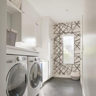 Cette image montre une petit buanderie design avec un placard à porte plane, des portes de placard blanches, un sol en carrelage de porcelaine, des machines côte à côte, un sol gris, un mur multicolore, un plan de travail blanc et du papier peint.
