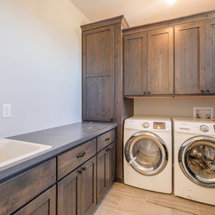 Design ideas for a mid-sized country u-shaped dedicated laundry room in Denver with a drop-in sink, shaker cabinets, dark wood cabinets, solid surface benchtops, grey walls, ceramic floors and a side-by-side washer and dryer.