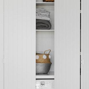 Esempio di una piccola lavanderia multiuso contemporanea con ante lisce, ante bianche, top in cemento, pareti bianche, pavimento in legno massello medio e lavatrice e asciugatrice nascoste