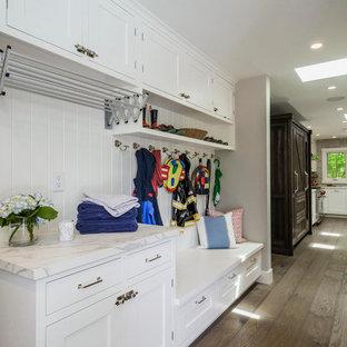 Exemple d'une grand buanderie parallèle chic multi-usage avec un évier de ferme, un placard à porte shaker, des portes de placard blanches, un mur gris, un sol en bois foncé et des machines superposées.