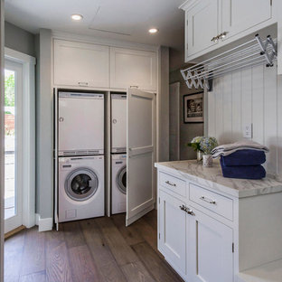 This is an example of a large classic galley utility room in San Francisco with shaker cabinets, white cabinets, grey walls, dark hardwood flooring and a stacked washer and dryer.