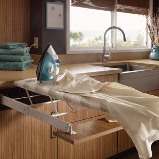 Foto di una piccola lavanderia contemporanea con lavello stile country, ante lisce, ante in legno chiaro, top in laminato e moquette
