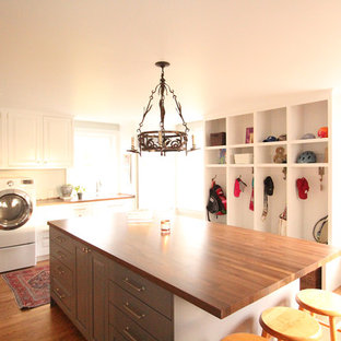 Photo of a large traditional l-shaped utility room in Other with a built-in sink, raised-panel cabinets, white cabinets, wood worktops, grey walls, medium hardwood flooring, a side by side washer and dryer and brown floors.