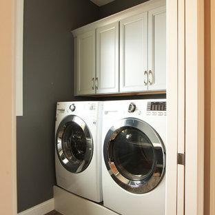 Ispirazione per una piccola sala lavanderia tradizionale con ante con riquadro incassato, ante beige, top in quarzo composito, pareti grigie, pavimento in gres porcellanato, lavatrice e asciugatrice affiancate, pavimento marrone e top bianco