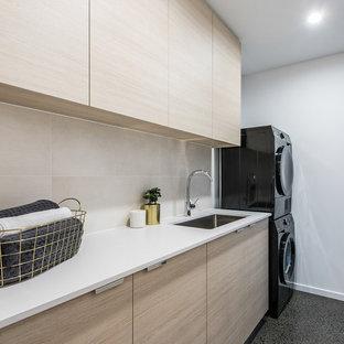 Ispirazione per una sala lavanderia minimal con lavello sottopiano, ante lisce, pareti bianche, lavatrice e asciugatrice a colonna, pavimento grigio e ante in legno chiaro