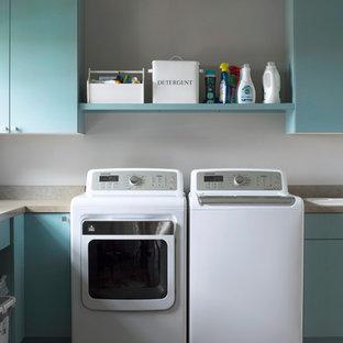 Idéer för vintage beige tvättstugor enbart för tvätt, med släta luckor, blå skåp, en nedsänkt diskho, en tvättmaskin och torktumlare bredvid varandra och laminatbänkskiva