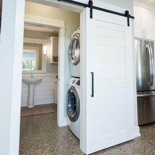 Foto di una piccola sala lavanderia chic con paraspruzzi bianco, paraspruzzi con piastrelle in ceramica, pavimento in cemento, pavimento grigio, lavatrice e asciugatrice a colonna e pareti grigie
