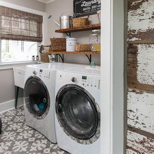 Immagine di una sala lavanderia country con lavatoio, lavatrice e asciugatrice affiancate, pavimento grigio e pareti grigie