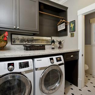 Immagine di una piccola lavanderia multiuso american style con ante lisce, ante grigie, top in granito, pareti grigie, pavimento con piastrelle in ceramica e lavatrice e asciugatrice affiancate