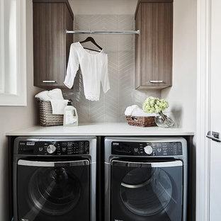 Immagine di una piccola sala lavanderia minimal con ante lisce, ante in legno scuro, top in quarzite, pareti beige, pavimento con piastrelle in ceramica, lavatrice e asciugatrice affiancate e pavimento grigio
