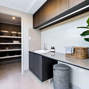 This is an example of a large contemporary single-wall utility room in Perth with a drop-in sink, flat-panel cabinets, grey cabinets, white walls, beige floor and grey benchtop.
