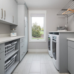 Inspiration for a transitional galley dedicated laundry room in Grand Rapids with flat-panel cabinets, grey cabinets, quartzite benchtops, porcelain floors, a side-by-side washer and dryer, grey floor and white benchtop.
