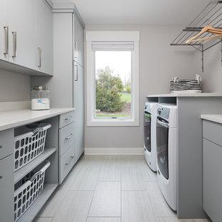 Idéer för att renovera en vintage vita parallell vitt tvättstuga enbart för tvätt, med släta luckor, grå skåp, bänkskiva i kvartsit, klinkergolv i porslin, en tvättmaskin och torktumlare bredvid varandra och grått golv
