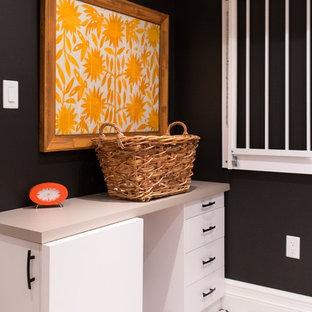 Foto di un ripostiglio-lavanderia minimal di medie dimensioni con lavello sottopiano, ante lisce, top in laminato, pareti nere, pavimento con piastrelle in ceramica, lavatrice e asciugatrice affiancate, pavimento bianco e ante bianche