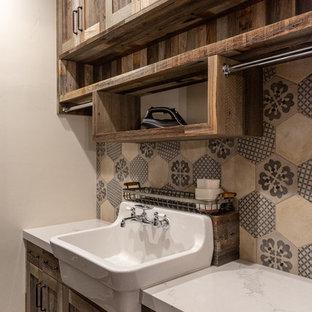 Immagine di una sala lavanderia stile rurale con lavello stile country, ante in legno scuro, pareti beige e top bianco