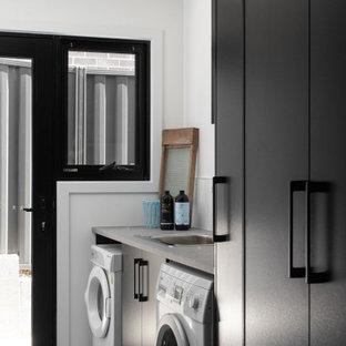 Modern inredning av en grå grått tvättstuga enbart för tvätt, med släta luckor, svarta skåp, vita väggar, en tvättmaskin och torktumlare bredvid varandra och grått golv