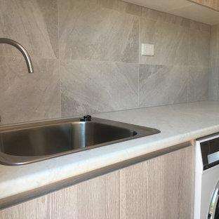 Inspiration för små moderna linjära grått tvättstugor enbart för tvätt och med garderob, med en nedsänkt diskho, släta luckor, skåp i ljust trä, laminatbänkskiva, grå väggar, klinkergolv i keramik och svart golv