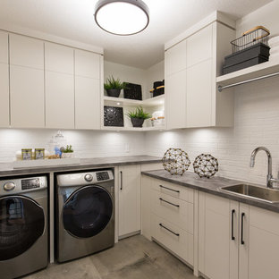 Example of a large trendy l-shaped dedicated laundry room design in Calgary with a drop-in sink, flat-panel cabinets, white cabinets, laminate countertops, white walls, a side-by-side washer/dryer and gray countertops