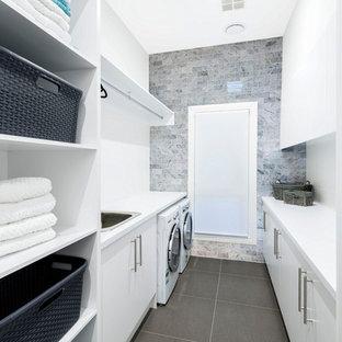 Immagine di una piccola sala lavanderia minimal con lavello da incasso, pareti bianche, pavimento con piastrelle in ceramica, ante lisce, ante bianche e lavatrice e asciugatrice affiancate