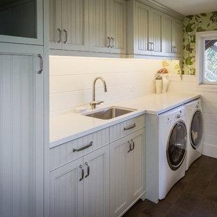 Lantlig inredning av en mellanstor linjär tvättstuga enbart för tvätt, med vita skåp, laminatbänkskiva, en tvättmaskin och torktumlare bredvid varandra, luckor med infälld panel, en undermonterad diskho och gröna väggar