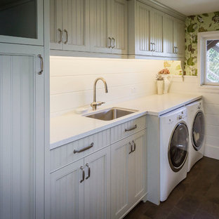 Photo of a mid-sized country single-wall dedicated laundry room in San Francisco with white cabinets, laminate benchtops, a side-by-side washer and dryer, recessed-panel cabinets, an undermount sink and green walls.