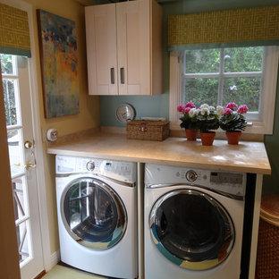 Klassisk inredning av ett litet parallellt grovkök, med marmorbänkskiva, en tvättmaskin och torktumlare bredvid varandra, skåp i shakerstil, skåp i ljust trä och blå väggar