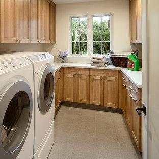 Immagine di una lavanderia mediterranea con ante in stile shaker, ante in legno chiaro, lavatrice e asciugatrice affiancate e top bianco