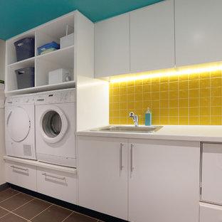 Foto på en mellanstor funkis linjär tvättstuga enbart för tvätt, med en nedsänkt diskho, släta luckor, vita skåp, laminatbänkskiva, klinkergolv i keramik och en tvättmaskin och torktumlare bredvid varandra