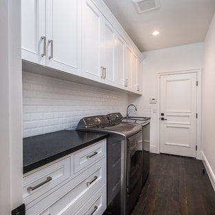 Medium sized traditional single-wall separated utility room in Orange County with a submerged sink, marble worktops, white walls, dark hardwood flooring, a side by side washer and dryer, brown floors, black worktops, recessed-panel cabinets and white cabinets.