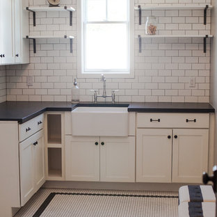 Example of a mid-sized classic l-shaped ceramic tile dedicated laundry room design in Phoenix with a farmhouse sink, shaker cabinets, white cabinets, granite countertops, gray walls and a side-by-side washer/dryer