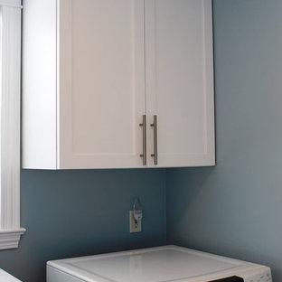Idée de décoration pour une buanderie design multi-usage et de taille moyenne avec un évier encastré, un placard à porte shaker, des portes de placard blanches, un plan de travail en quartz modifié, une crédence multicolore, un mur bleu, un sol en bois clair et des machines côte à côte.