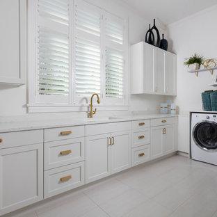 Inredning av en klassisk vita l-formad vitt tvättstuga, med en undermonterad diskho, skåp i shakerstil, vita skåp, vita väggar och vitt golv