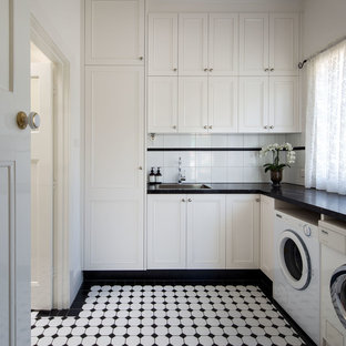 Mid-sized elegant l-shaped ceramic tile and white floor dedicated laundry room photo in Melbourne with a drop-in sink, shaker cabinets, white cabinets, granite countertops, white walls and a side-by-side washer/dryer