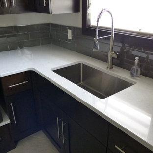Modern inredning av en mellanstor linjär tvättstuga enbart för tvätt, med en undermonterad diskho, luckor med infälld panel, skåp i mörkt trä, bänkskiva i kvarts, grå väggar, klinkergolv i keramik och en tvättmaskin och torktumlare bredvid varandra