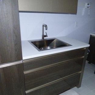 Idéer för att renovera en mycket stor funkis u-formad tvättstuga, med en undermonterad diskho, släta luckor, grå skåp, bänkskiva i kvarts, blått stänkskydd, stänkskydd i glaskakel och marmorgolv