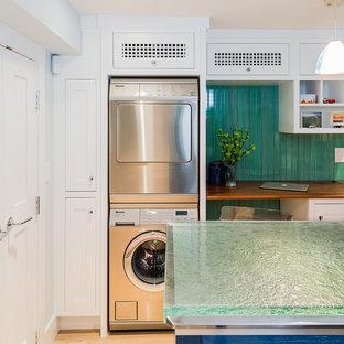 Идея дизайна: отдельная прачечная среднего размера в стиле современная классика с белыми фасадами, стеклянной столешницей, зелеными стенами, светлым паркетным полом, с сушильной машиной на стиральной машине, фасадами в стиле шейкер и бирюзовой столешницей