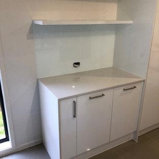 Modern inredning av en liten beige linjär beige tvättstuga, med släta luckor, vita skåp, laminatbänkskiva, vitt stänkskydd, glaspanel som stänkskydd, vita väggar och klinkergolv i keramik