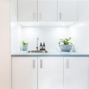 Foto di una piccola sala lavanderia classica con lavello da incasso, ante bianche, top in laminato, pareti bianche, parquet chiaro, lavasciuga, pavimento beige e top turchese