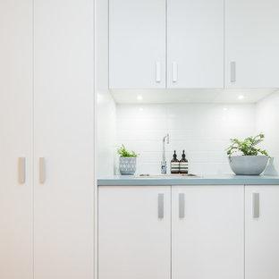 Ispirazione per una piccola sala lavanderia classica con lavello da incasso, ante bianche, top in laminato, pareti bianche, parquet chiaro, lavasciuga, pavimento beige e top turchese