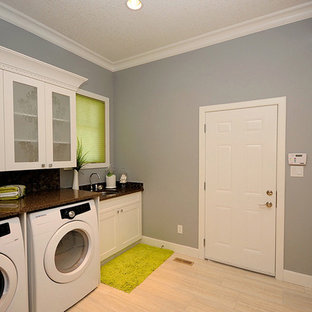 Design ideas for a medium sized contemporary single-wall utility room in Edmonton with a submerged sink, shaker cabinets, white cabinets, terrazzo worktops, grey walls, porcelain flooring, a side by side washer and dryer and beige floors.