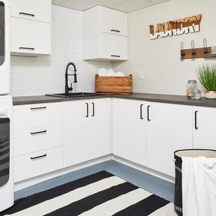 Inredning av en lantlig grå l-formad grått tvättstuga enbart för tvätt, med en nedsänkt diskho, släta luckor, vita skåp, grå väggar, en tvättpelare och blått golv