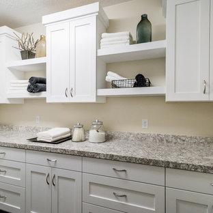 Inredning av en modern mellanstor tvättstuga enbart för tvätt, med skåp i shakerstil, vita skåp, granitbänkskiva, beige väggar, vinylgolv och en tvättmaskin och torktumlare bredvid varandra