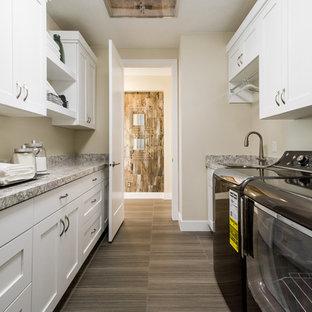 Idéer för att renovera en mellanstor funkis parallell tvättstuga enbart för tvätt, med en undermonterad diskho, skåp i shakerstil, vita skåp, granitbänkskiva, beige väggar, vinylgolv och en tvättmaskin och torktumlare bredvid varandra