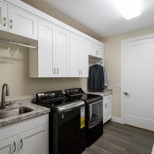 Immagine di una sala lavanderia contemporanea di medie dimensioni con lavello sottopiano, ante in stile shaker, ante bianche, top in granito, pareti beige, pavimento in vinile e lavatrice e asciugatrice affiancate