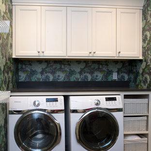 Inspiration för stora 60 tals u-formade tvättstugor enbart för tvätt, med luckor med infälld panel, vita skåp, bänkskiva i onyx, en tvättmaskin och torktumlare bredvid varandra, en undermonterad diskho, blå väggar och skiffergolv