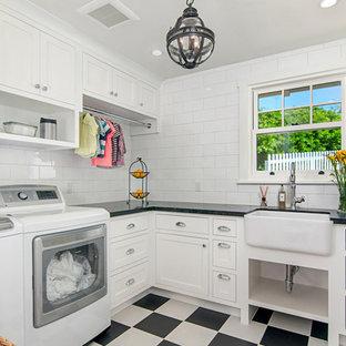 Exemple d'une petit buanderie chic en L dédiée avec un évier de ferme, des portes de placard blanches, un mur blanc, un sol en linoléum, des machines côte à côte, un sol multicolore, un plan de travail noir et un placard à porte shaker.