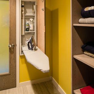 На фото: прачечная в современном стиле с желтыми стенами с