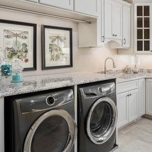 Idéer för ett stort klassiskt u-format grovkök, med släta luckor, vita skåp, granitbänkskiva, en tvättmaskin och torktumlare bredvid varandra och beiget golv
