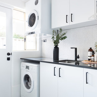 Inspiration for a mid-sized contemporary single-wall utility room in Perth with an undermount sink, flat-panel cabinets, white cabinets, white splashback, white walls, porcelain floors, a stacked washer and dryer, grey floor and black benchtop.