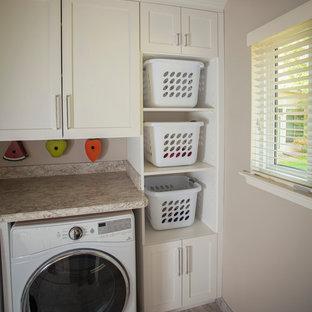 Exempel på en liten modern parallell tvättstuga enbart för tvätt, med en rustik diskho, vita skåp, granitbänkskiva, beige väggar, en tvättmaskin och torktumlare bredvid varandra, beiget golv, klinkergolv i keramik och skåp i shakerstil